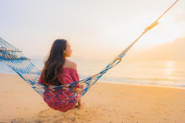 Женщина портрета красивая молодая азиатская сидя на гамаке с морем и oce пляжа neary улыбки счастливым