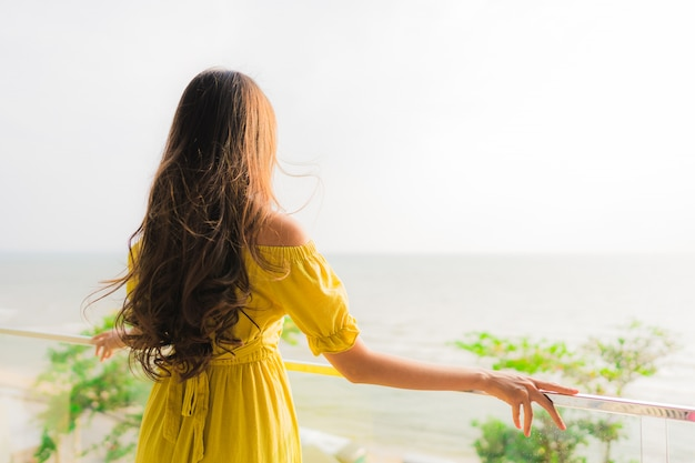 Улыбка женщины портрета красивая молодая азиатская счастливая и ослабляет на внешнем балконе с пляжем моря и oce