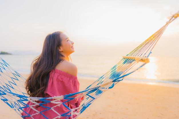 笑顔幸せなニアリービーチ海とoceでハンモックに座っている肖像画