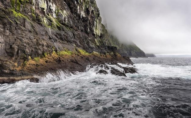 暗い雲の下の岩山の前の海