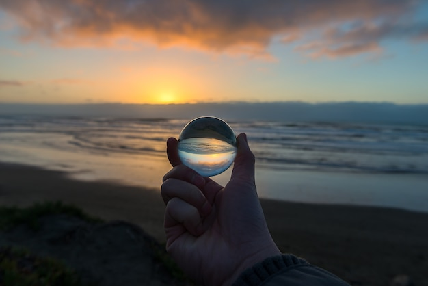 Ocean beach sunset in the crystal ball holding in my hand