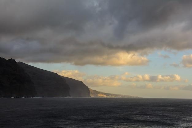 바다 해안입니다. 태양이 비추는 산속의 만