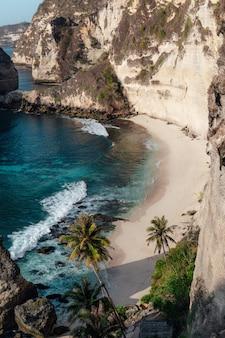 Oceano che colpisce la spiaggia sabbiosa circondata da scogliere