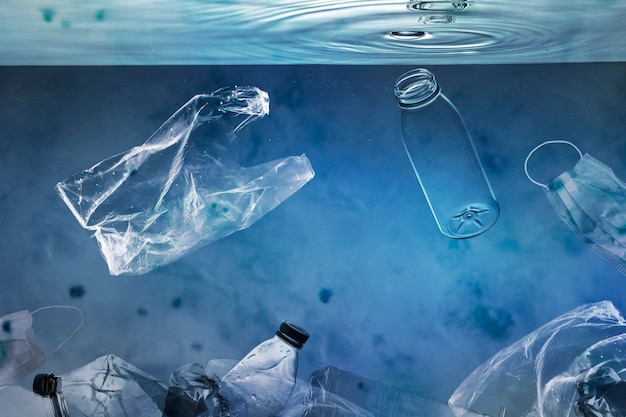 Ocean pollution campaign with plastic bags and used bottles floating