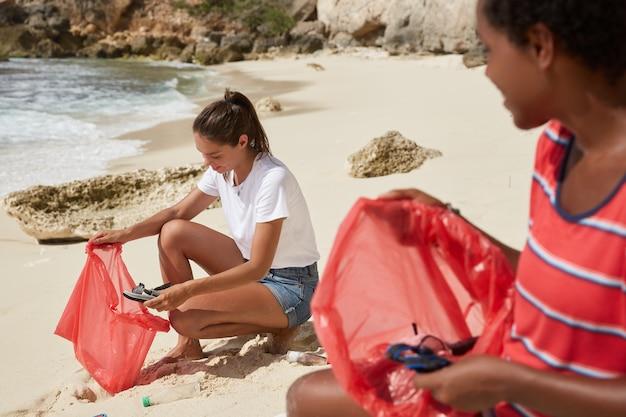 海洋汚染の概念。忙しいボランティアのクロップドショットは、古い靴やその他のゴミをバッグに入れて拾います