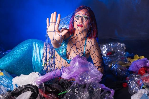 Ocean pollution, rubbish in the water. sad fairytale mermaid in dirty ocean.