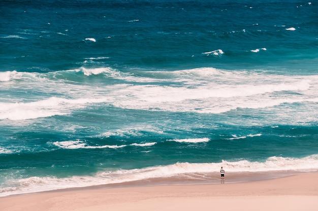 大きなターコイズブルーの波が釣り竿で立っている遠くの漁師と海の砂のビーチ