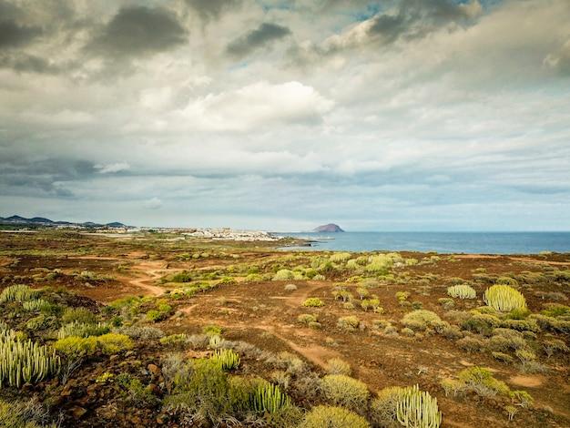 熱帯地方の田園地帯からのオーシャンビュー。乾燥地のカークスと草の植物。天候の変化。観光客のための雲と海の海岸線の画像と美しい空