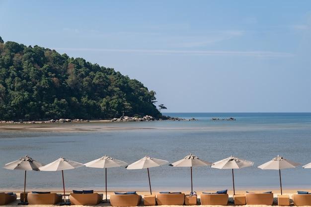 Вид на океан, море с зонтиком голубого неба и кресло почти на пляже.