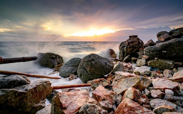 美しい夕焼け空と雲と岩のビーチで海の水のしぶき