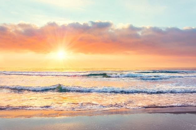 Ocean wave on the beach at sunset time, sun rays.