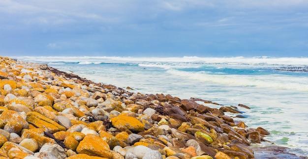 南アフリカのケープタウンで捕獲された岩に覆われた海岸にやってくる海の波