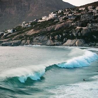 Океанские волны падают на скалистый берег днем новое фото