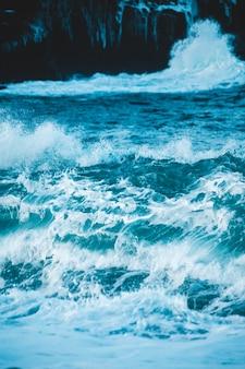Океанские волны разбиваются о берег в дневное время
