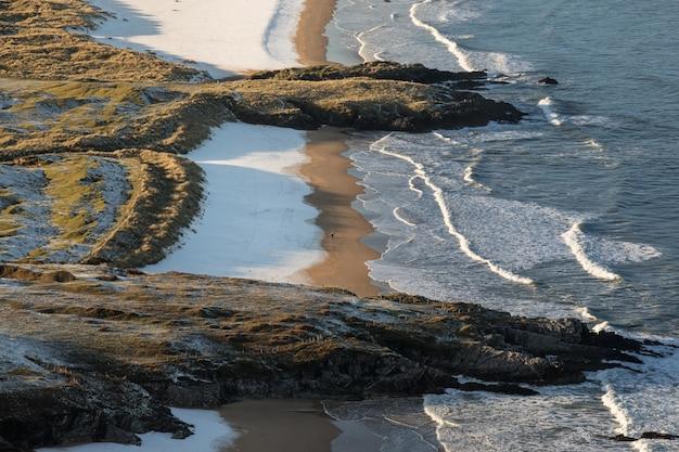 Океанские волны разбиваются о скалистый берег