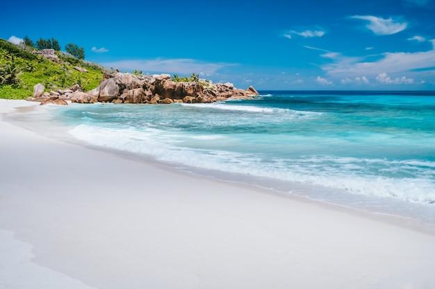 アンスココビーチの海の波、手付かずの青い色のラグーン、花崗岩の岩