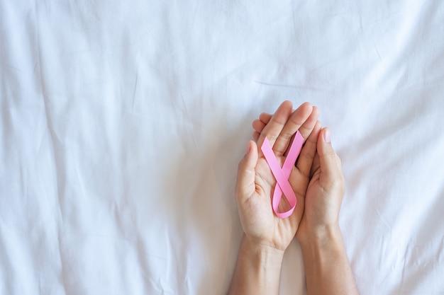 10月の乳がん啓発月間、ピンクの背景にピンクのリボンを持っている大人の女性の手は、生きている人々と病気をサポートするために。国際女性、母と世界の癌デーの概念