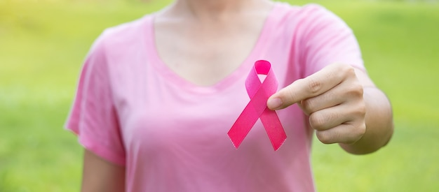 October breast cancer awareness month, adult woman in pink t- shirt with hand holding pink ribbon for supporting people living and illness. international women, mother and world cancer day concept