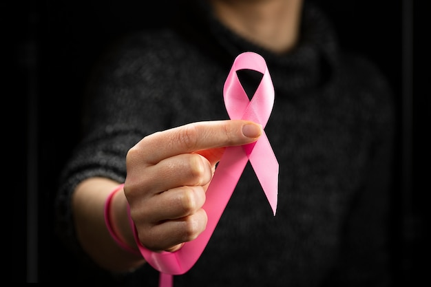 October breast cancer awareness month, an adult woman wearing a dark t-shirt with a pink ribbon in her hand to support people living and sick