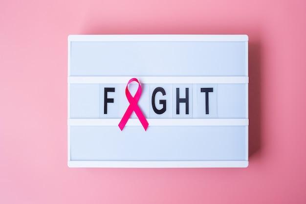Октябрь, месяц осведомленности о раке груди, розовая лента на лайтбоксе с текстовым фоном «борьба» для поддержки людей, живущих и больных. концепция международного дня борьбы с раком женщины, матери и мира