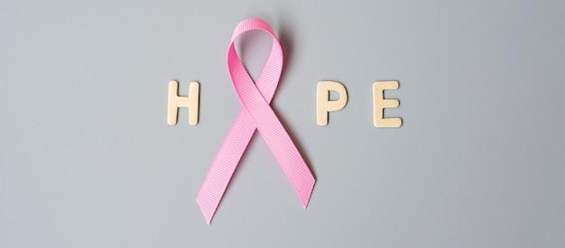 Октябрь месяц осведомленности о раке груди, розовая лента с текстом надежда на сером фоне для поддержки людей, живущих и больных. концепция международного дня борьбы с раком женщины, матери и мира
