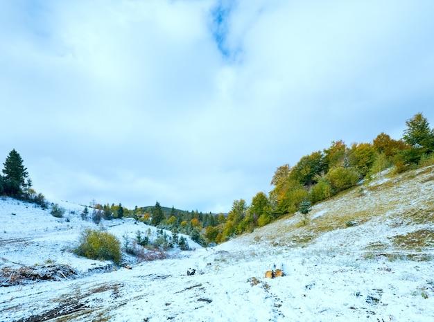Октябрьские карпаты с первым зимним снегом на грязной дороге