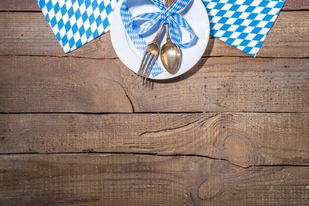 10월 축제 컨셉입니다. 옥토버페스트 테이블 설정 배경, 전통 냅킨이 있는 접시 포크 스푼, 이벤트 제공, 바 메뉴 플랫레이, 흰색 나무 테이블 복사 공간 위쪽 전망