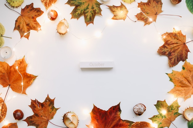Октябрьская плоская планировка и осенняя композиция с листьями, свечами и каштанами, вид сверху