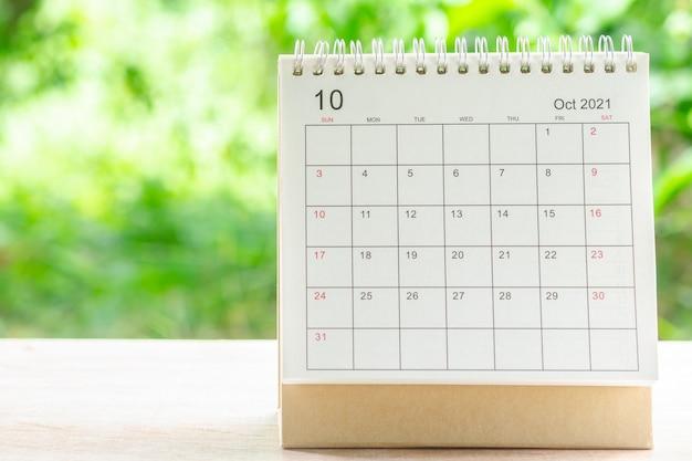 10월 달, 주최자를 위한 캘린더 데스크 2021은 녹색 자연 배경을 가진 나무 테이블에 대한 계획 및 알림을 제공합니다.