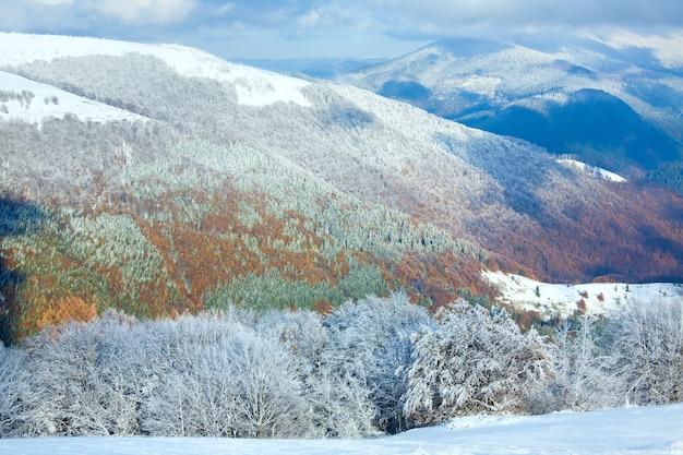 Октябрьский горный буковый лес на опушке с первым зимним снегом и разноцветной листвой прошлой осенью на дальнем склоне горы