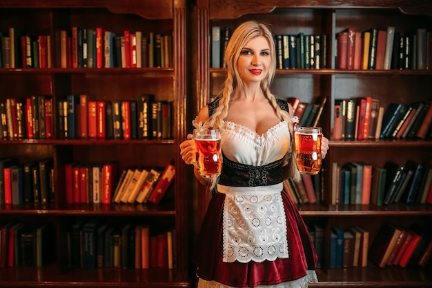 Octoberfest waitress with two mugs of fresh beer standing against shelf with books in vintage pub.