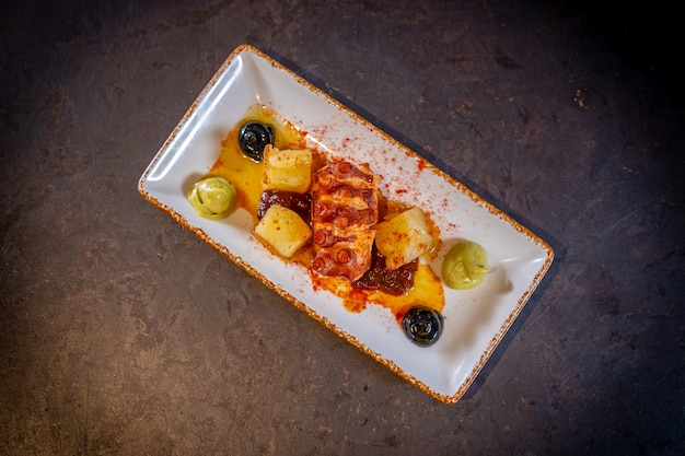 Octopus tentacle with potatoes on a black background, on a white plate