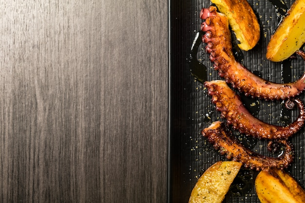 Octopus tentacles grilled with potatoes. copy space
