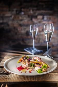 식전주와 함께 하얀 접시에 야채 샐러드와 문 어. 레스토랑에서 식사의 요리 서빙.