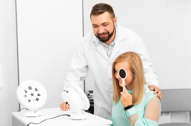 Окулист осматривает девочку-подростка с диагностическим оборудованием в клинике