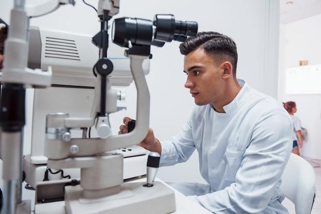 Окулист проверяет зрение пациента с помощью специального современного аппарата.