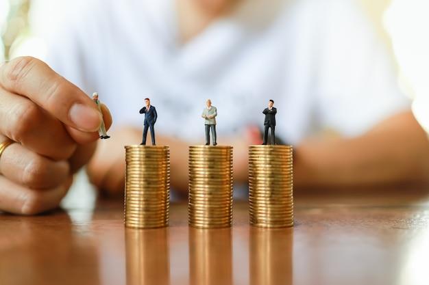 ビジネス、お金および人間の管理リソースの概念。ビジネスマンのミニチュアフィギュアの人々を保持し、木製のテーブルにゴールドコインの上部のodスタックの図を変更するために置く人間の手のクローズアップ。