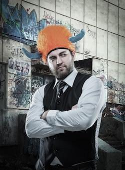 Странный бизнесмен в партийном шлеме со скрещенными руками