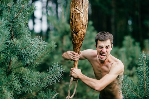 Odd primitive naked man with crazy face holding huge wooden stick in his hands in forest.