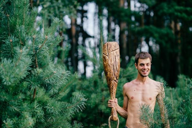 森で巨大な木の棒の狩猟で奇妙な原始的な裸の男。成人男性は手に失礼なクラブを持つ狂気のような精神を持っています。表情豊かな興奮した少年の顔。ワイルドで男性的な強さ。残酷な戦士