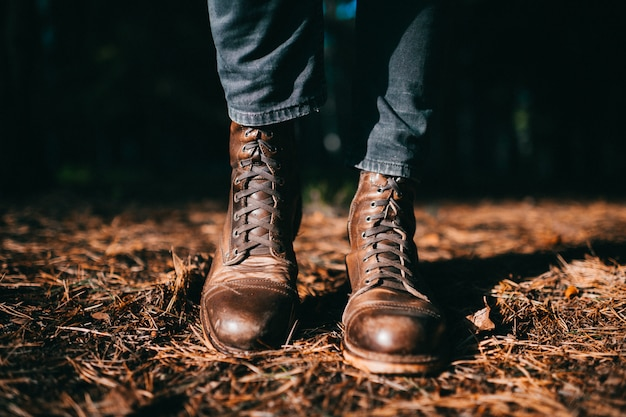 Odd woodcutter in vintage hipster masculine rough leather wooden boots standing in autumn forest on ground with dry orange spruce needles.