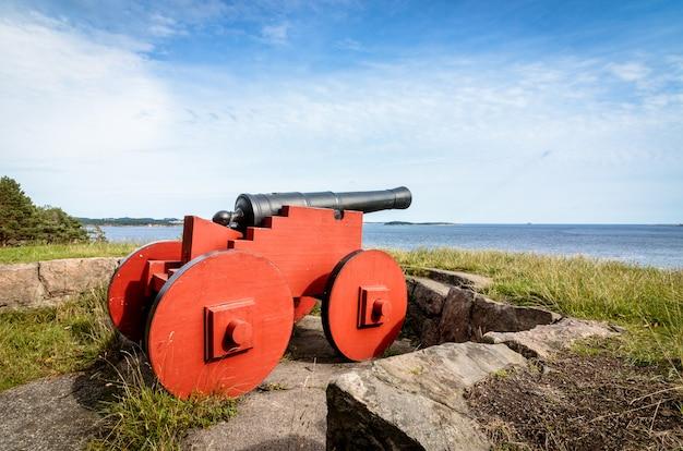 Красная пушка стоя на odderoya, kristiansand, норвегии. вид на море, голубое небо