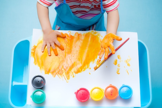 Oddler baby boy child finger painting with hands and watercolors