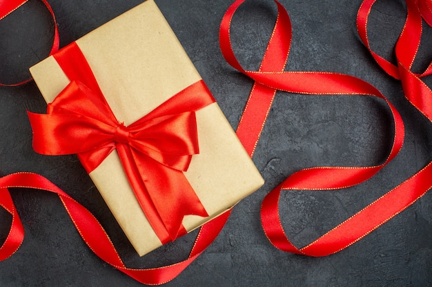 Oerhead view of stacked beautiful gift with red ribbon on dark background