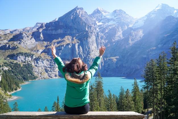 幸福アジアの若い旅行者ハイカーはoeschinensee湖の素晴らしい景色を楽しんでいます