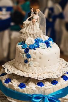 花嫁と花ofの姿を3層のバラで飾られた白いウェディングケーキ