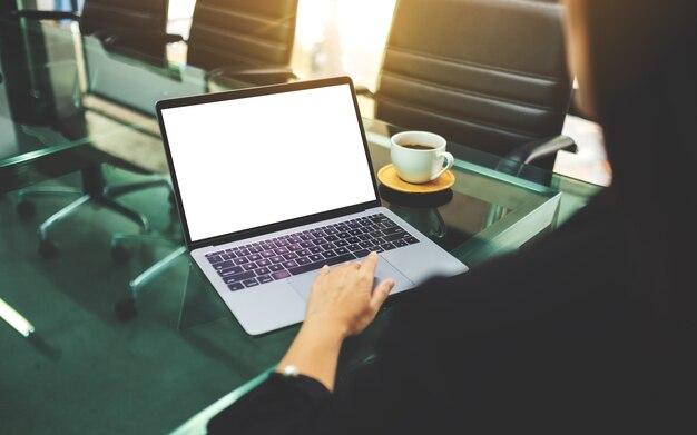 を使用して、オフィスで空白の白いデスクトップ画面でラップトップのタッチパッドに触れる実業家の肖像画