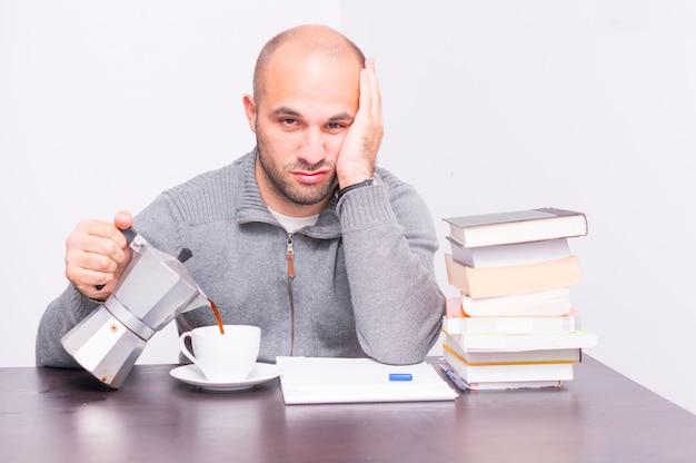 本の横にあるカップにコーヒーを注ぐ男の写真