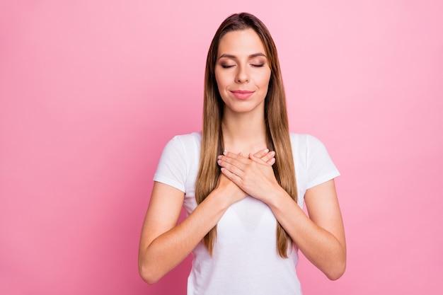 胸に手のひらを持って最高の心臓の感情を表現する驚くべき女性の平和な調和のとれた気分の目を閉じてカジュアルな白いtシャツを着る