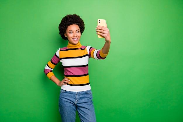 人気のあるオンラインウェブサイトのブログのselfiesを作る電話の手を握っている美しい暗い肌の巻き毛の女性のカジュアルなストライプのプルオーバージーンズを着用してください